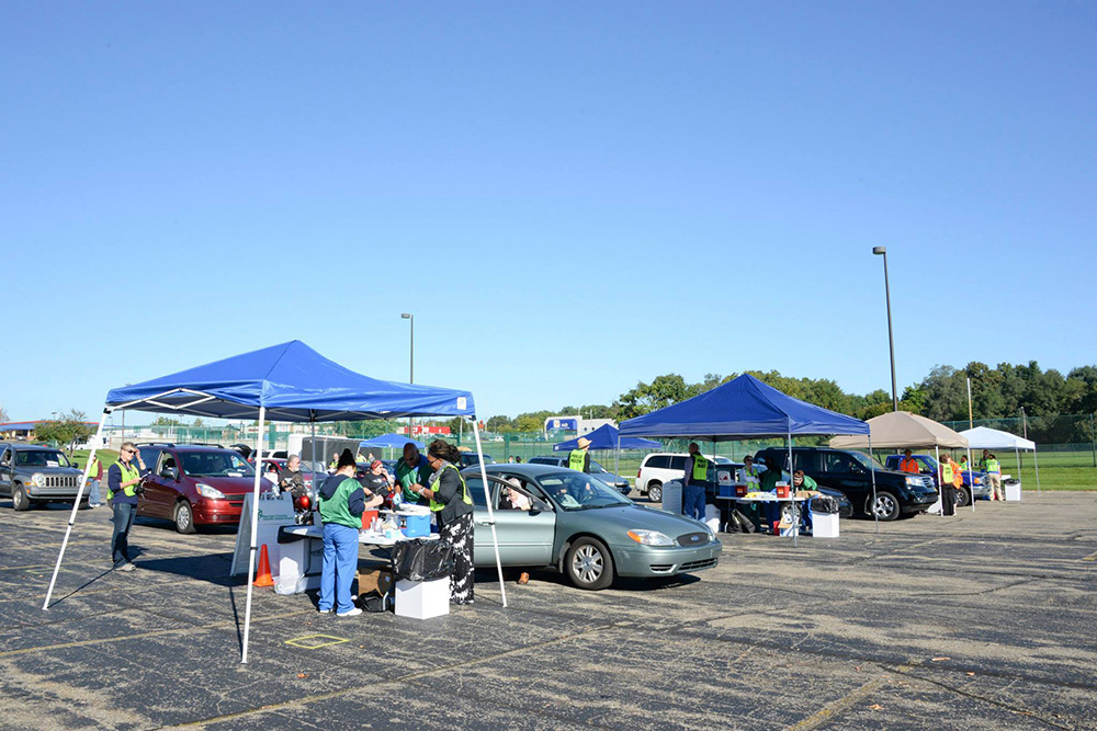 Health officials assist patients in their cars in a KCC parking lot during a drive-through flu-shot event.