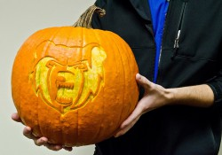 A student holds a pumpkin with a design of the KCC mascot Blaze carved into it.