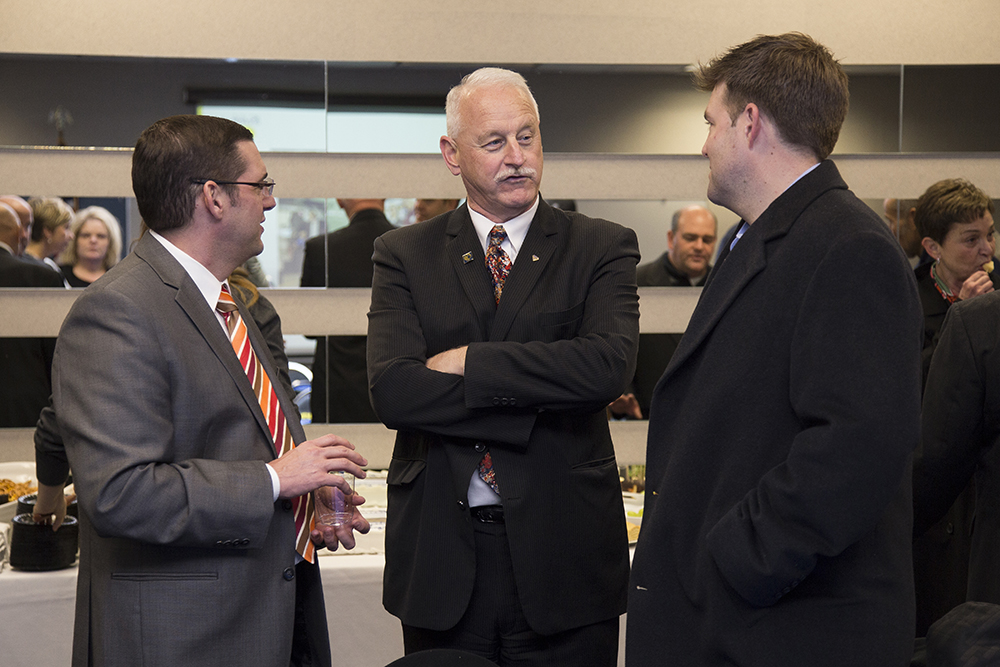 Mark O'Connell, center, converses with Bernhard Kerschbaum, Chief Executive Officer of Rosler Metal Finishing USA, left, and Drew Schweitzer, Vice President of Schweitzer Construction, right, during an event in November 2015. Photo by Sarah Huling.