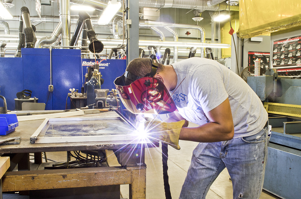 A KCC employee welds at the RMTC campus in Battle Creek.