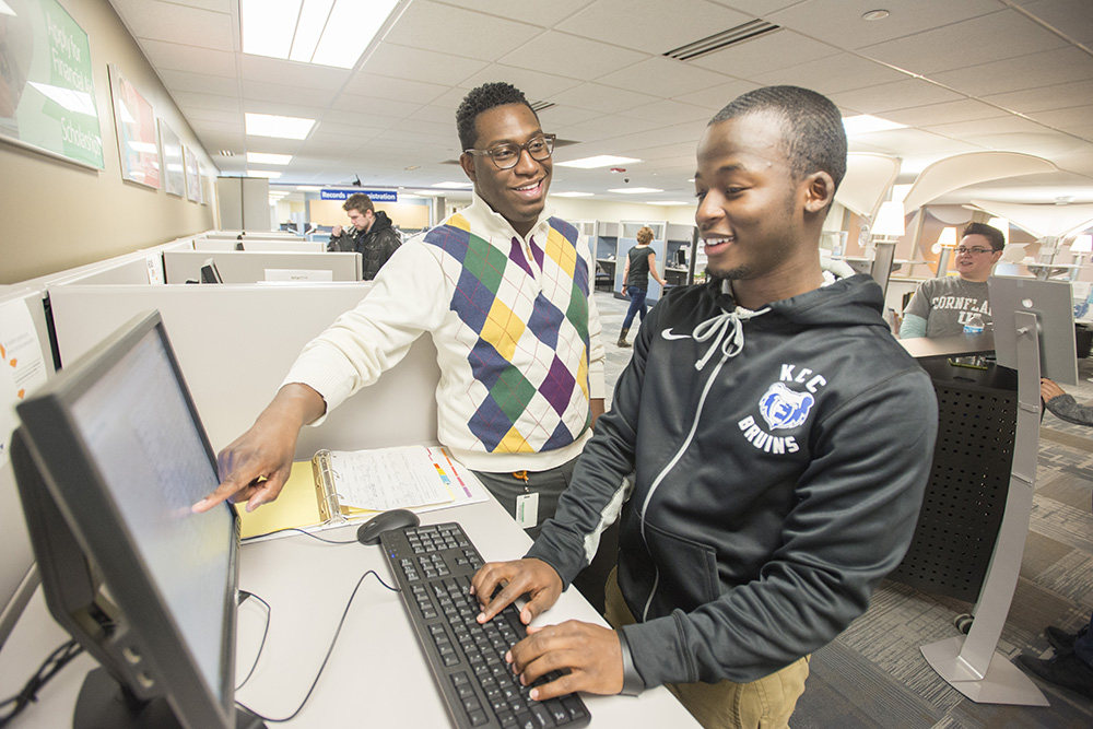 A KCC employee assists a student on a computer in the Hub.