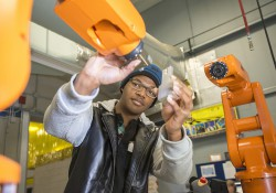 A KCC student demonstrates the use of a robot on KCC's RMTC campus in Battle Creek.