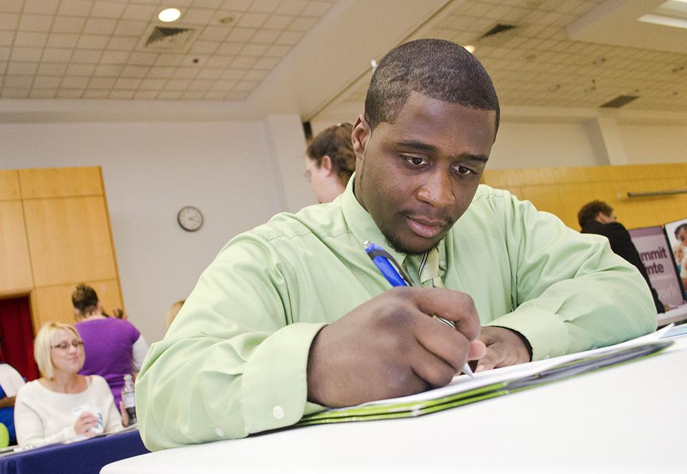 A job fair attendee fills out an application.