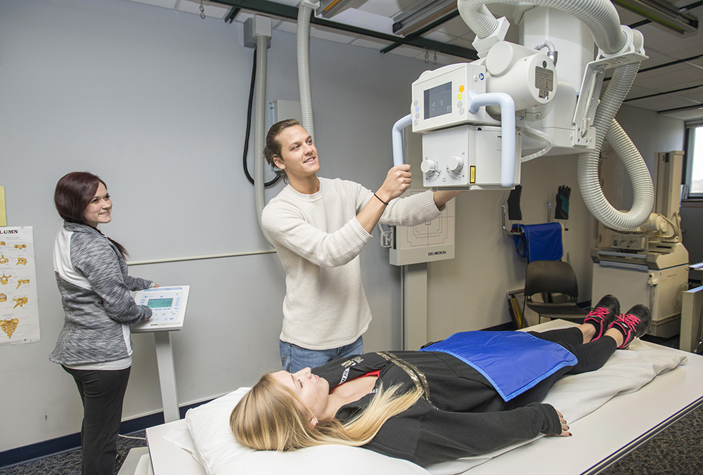 KCC Radiography students Ashley Ledford and Joshua Pitchure demonstrate the use of the program's new X-ray machine, while Radiography student Jennifer Whitaker acts as their patient.