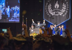 KCC President Mark O'Connell raises his hands to celebrate KCC's Class of 2016 during Commencement at Kellogg Arena.