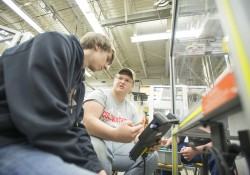 High school senior Kyle Myers holds a tablet-sized controller at the BACC as fellow senior Nick Pierucki points at the screen, giving instructions.