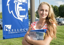 A student holding textbooks poses outside KCC's Grahl Center campus in Coldwater.