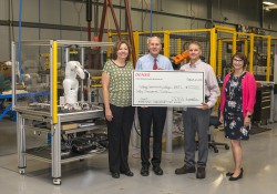 RMTC Director Tom Longman, second from the left, accepts grant funds from DENSO representatives at the RMTC in August.