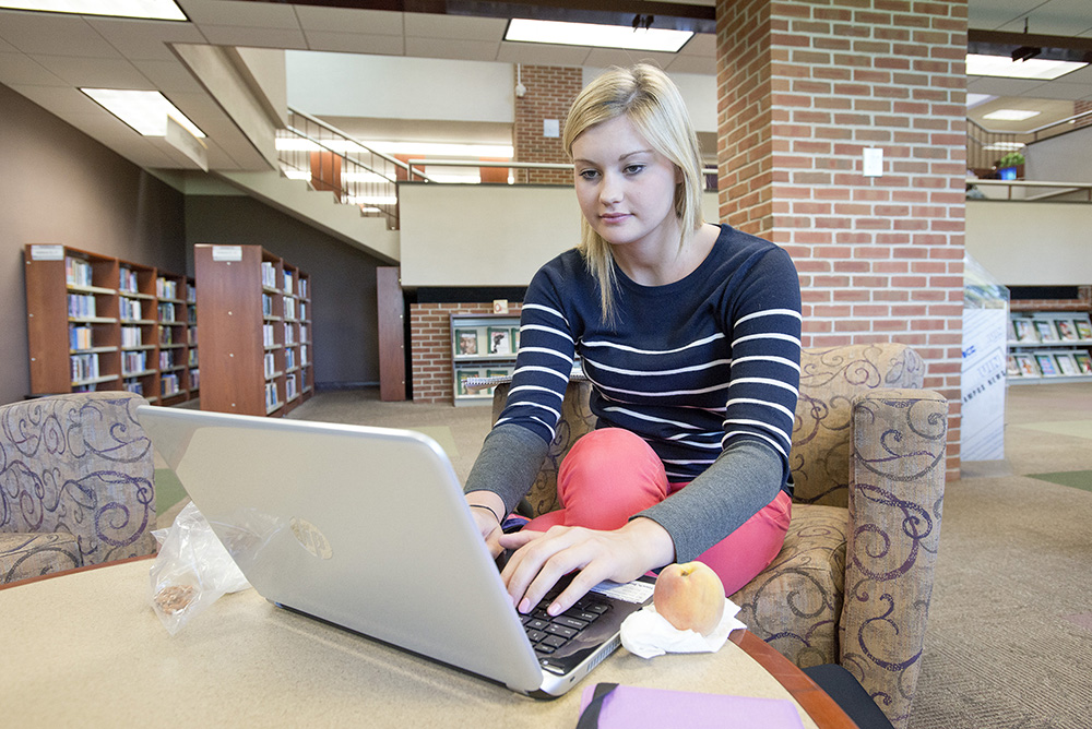 A student works on a laptop in the KCC library.