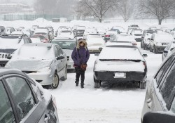 A student walks through a snowy KCC parking lot.