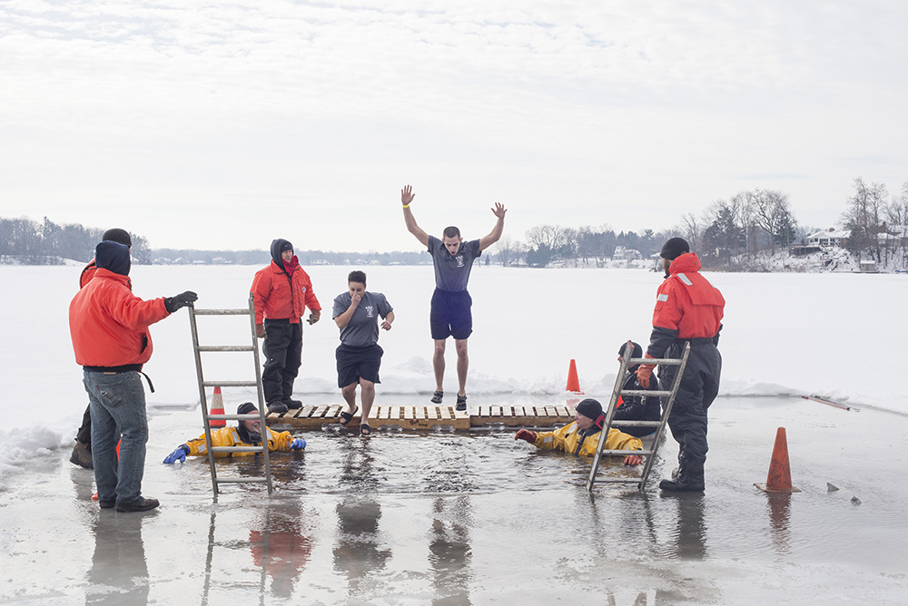 KCC Police Academy cadets jump into an icy lake during a Polar Plunge event to raise funds for Special Olympics Michigan.