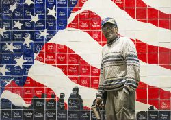 KCC alumnus Ron Leigh stands in front of an American flag mosaic at Silver Star Apartments in Battle Creek. Each tile includes the name of a resident at the facility, which houses homeless veterans.