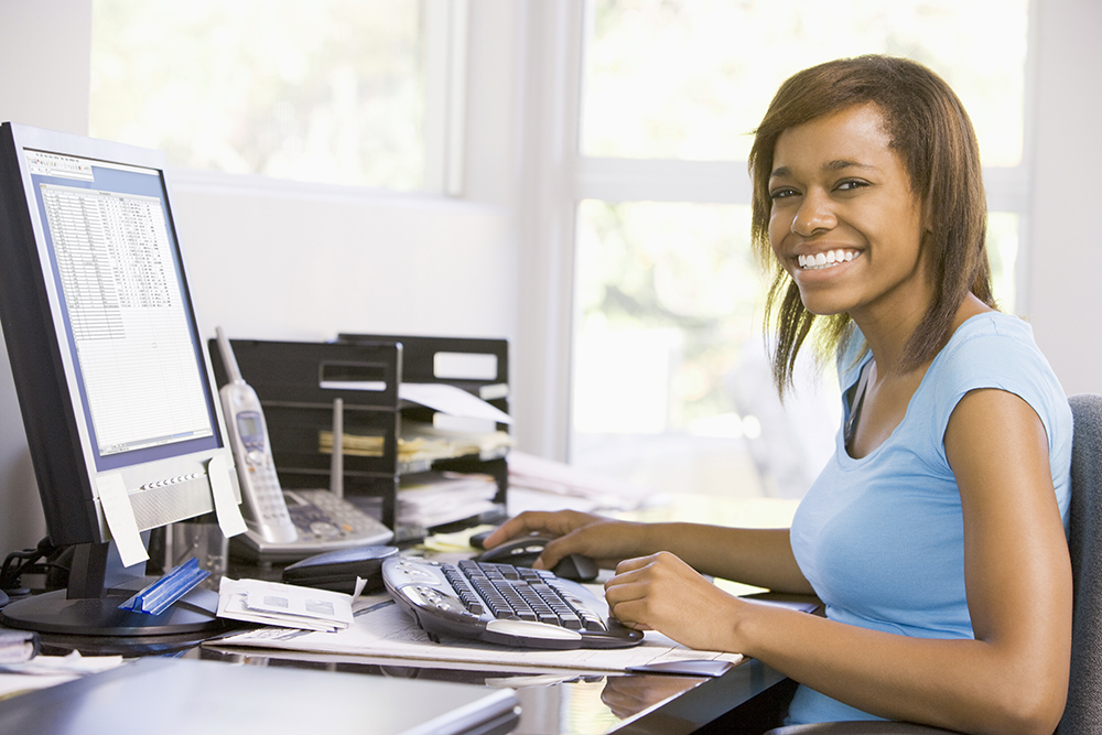 A woman sits in front of a computer, smiling.