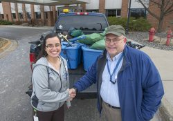 KCC Foundation Scholarship Technician Jackie Hallahan, left, shakes hands with area Boy Scouts of America troop leader Kevin Linders as Linders picks up a KCC Foundation donation on campus in Battle Creek.