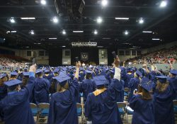 Graduates raise their hands in celebration following commencement.