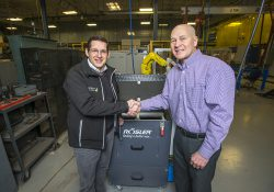 Rosler CEO Bernhard Kerschbaum, left, and RMTC Director Tom Longman shake hands in front of a new vibratory tub finishing machine donated by Rosler.