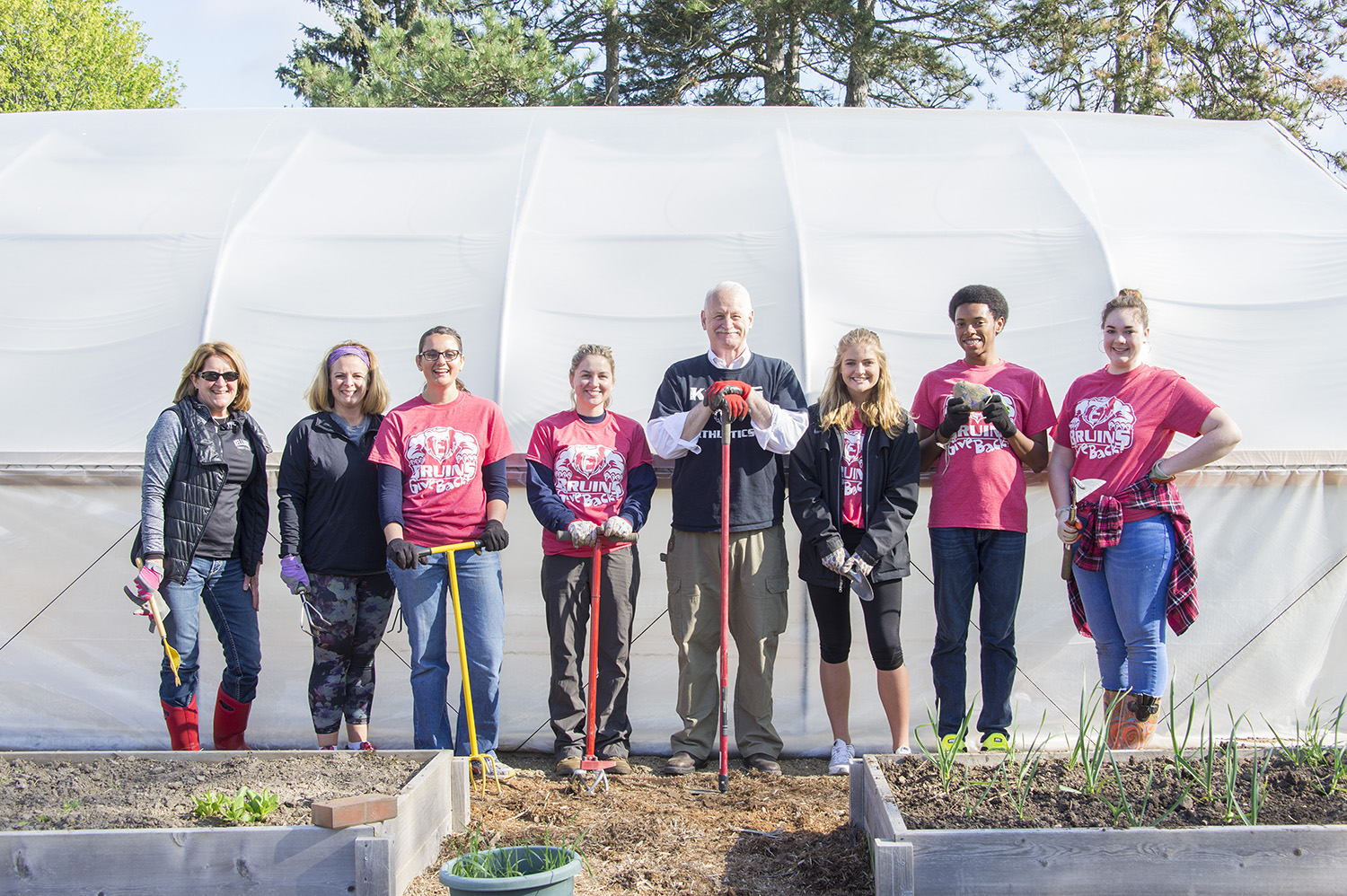Bruins Give Back participants pose while volunteering in KCC's community garden.