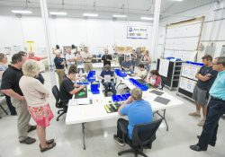 KAMA trainee family members, area employers, program funders and other community partners mingle and speak with the KAMA participants during a production run demonstration held during a meet-and-greet event at TNR Machine, Inc., in Dowling in July.