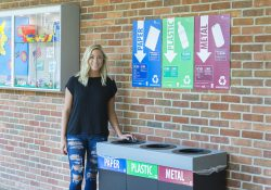 KCC alum Amber Hartlerode stands next to a new recycling station on KCC's North Avenue campus in Battle Creek.
