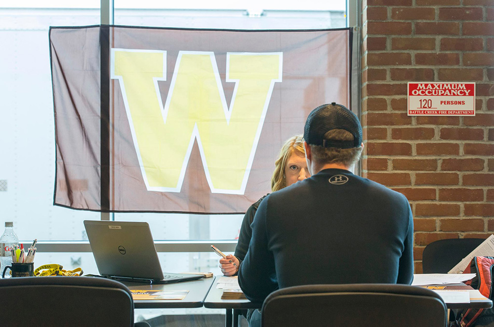 A representative from Western Michigan University assists a student during a WMU On-Site Admission Day event at KCC.