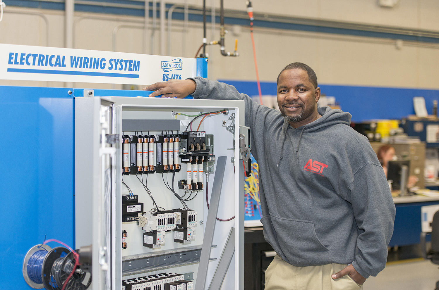 KCC student Anthony Gibbs poses with an electrical trainer at the RMTC campus in Battle Creek.