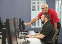 An instructor helps a student in a computer lab.