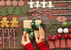 Stock photo featuring female hands over Christmas gifts and homemade gingerbread cookie with handmade decoration on a wooden background.