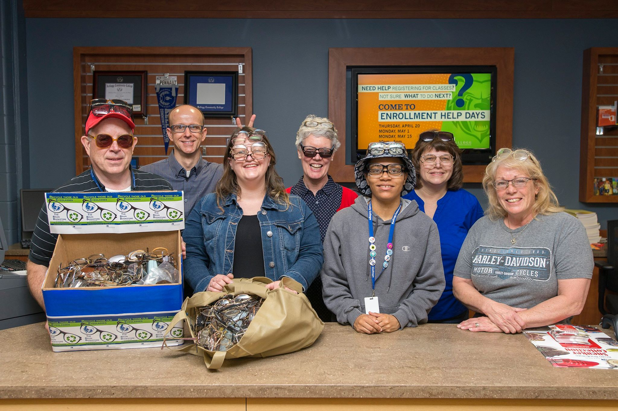 Bruin Bookstore staff pose with eyeglasses collected during a donation drive at KCC.
