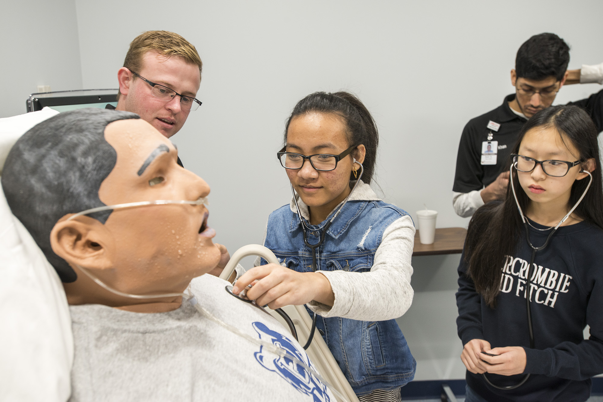 Lakeview Middle School student Van Tling checks the heartbeat of a patient simulator at Kellogg Community College while classmate Sarah Cha and Western Michigan University Homer Stryker M.D. School of Medicine student Zackary Cowan observe.