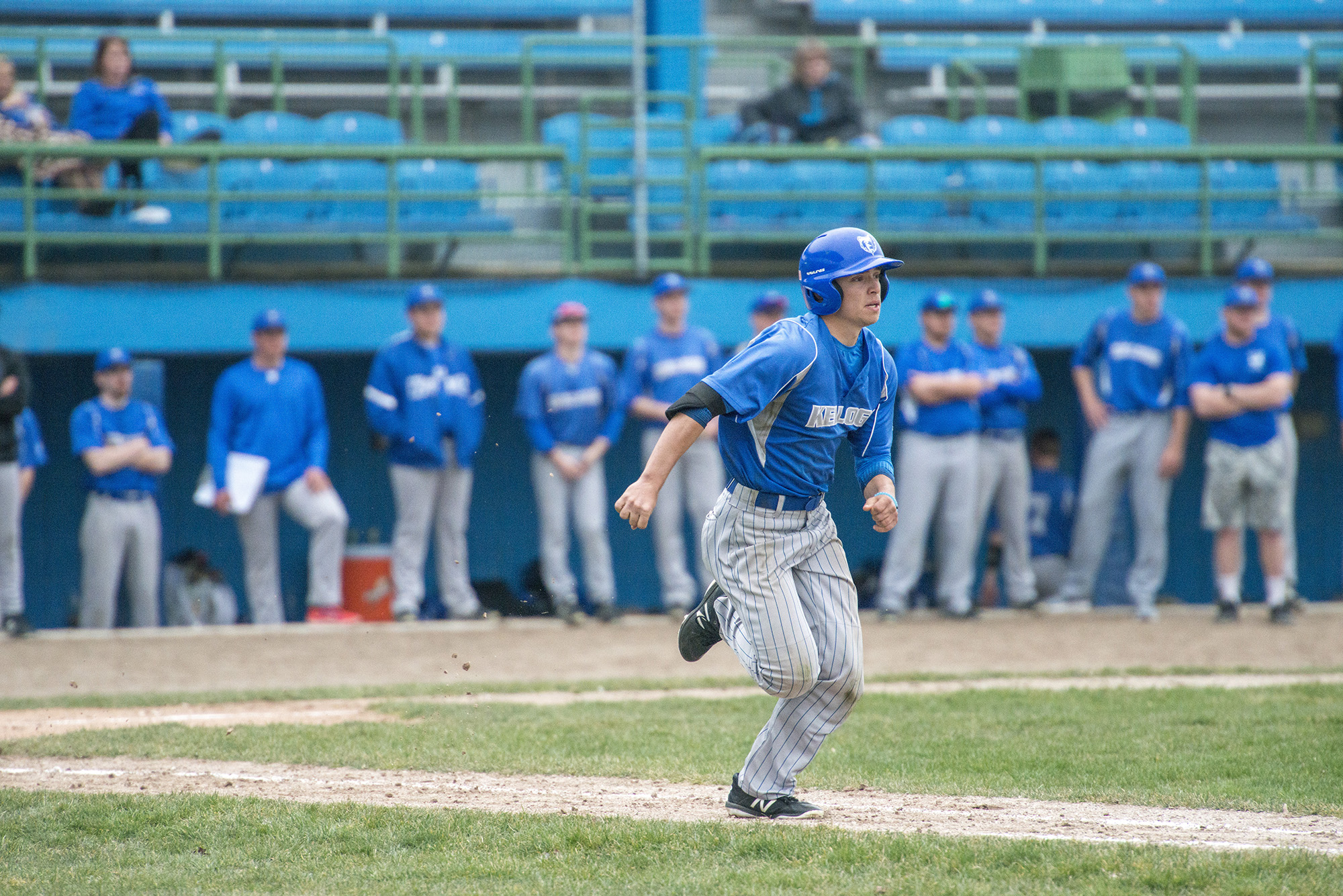 A KCC baseball player runs to first after hitting the ball during a home game.