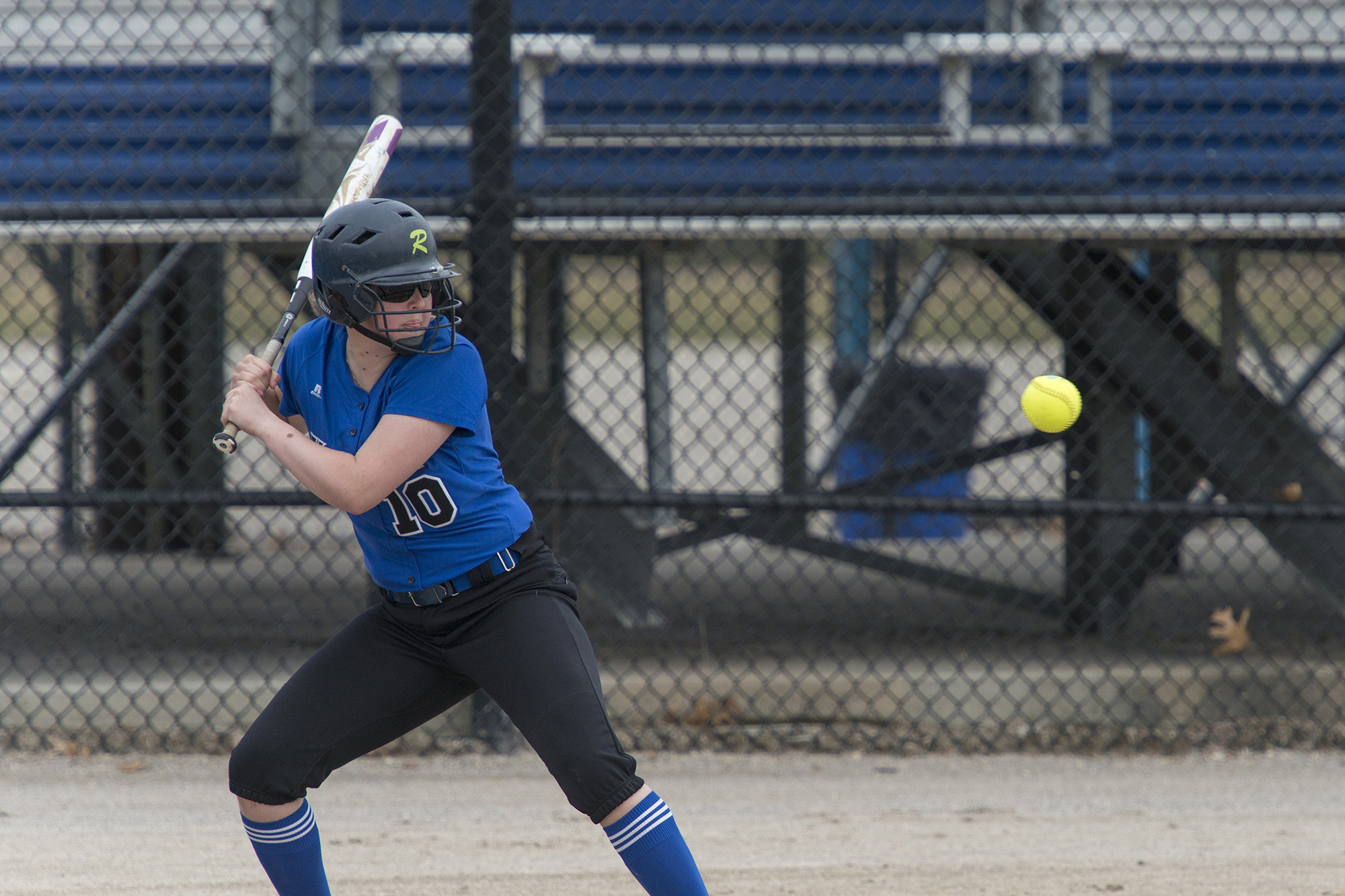 A KCC softball player bats during a home game.