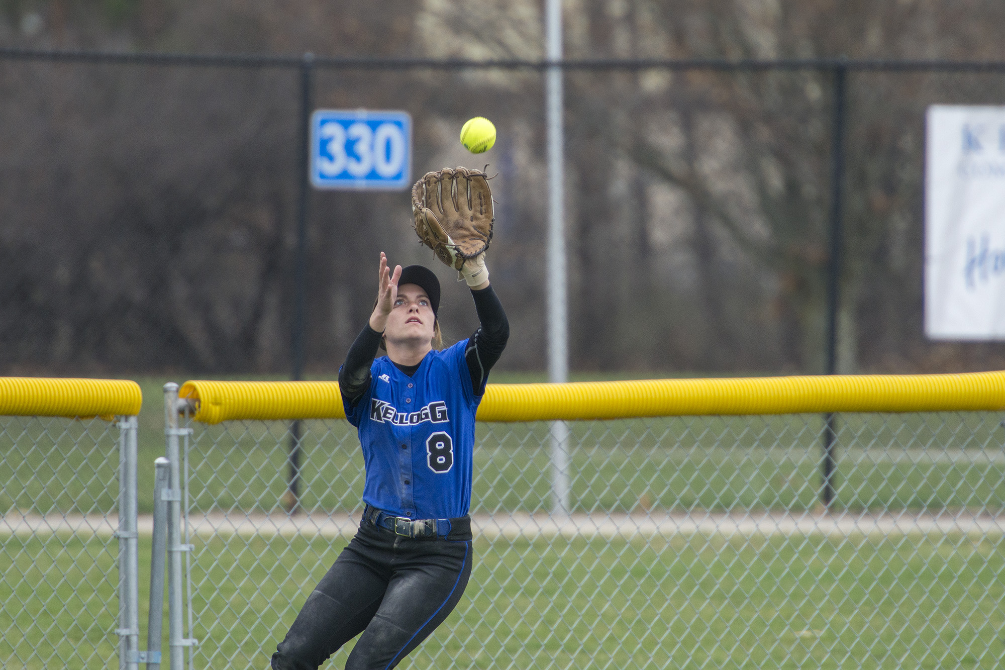 A KCC softball player catches a ball in the outfield during a home game at Bailey Park in Battle Creek.