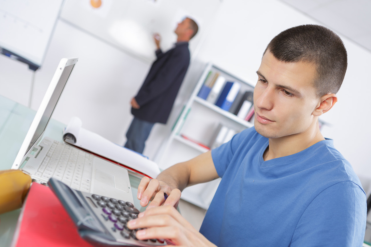 Stock photo of a male student working on a calculator during a class.