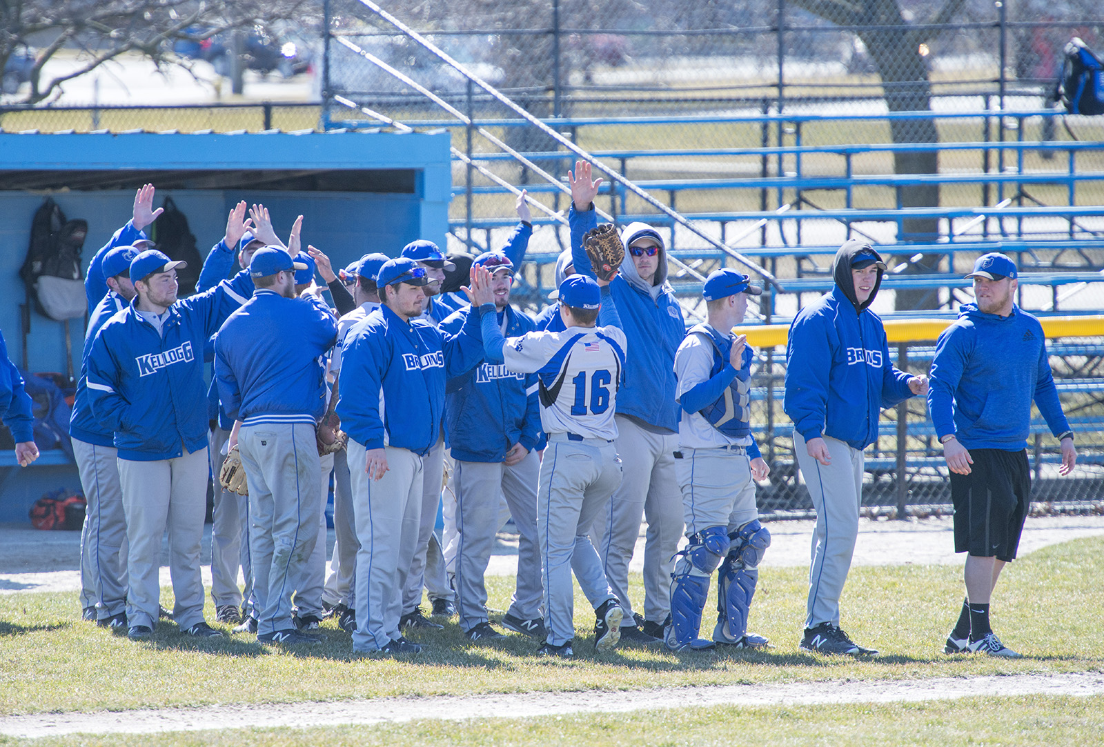 Members of KCC's baseball team congratulate players returning from the field between innings during a home game at Bailey Park in Battle Creek.