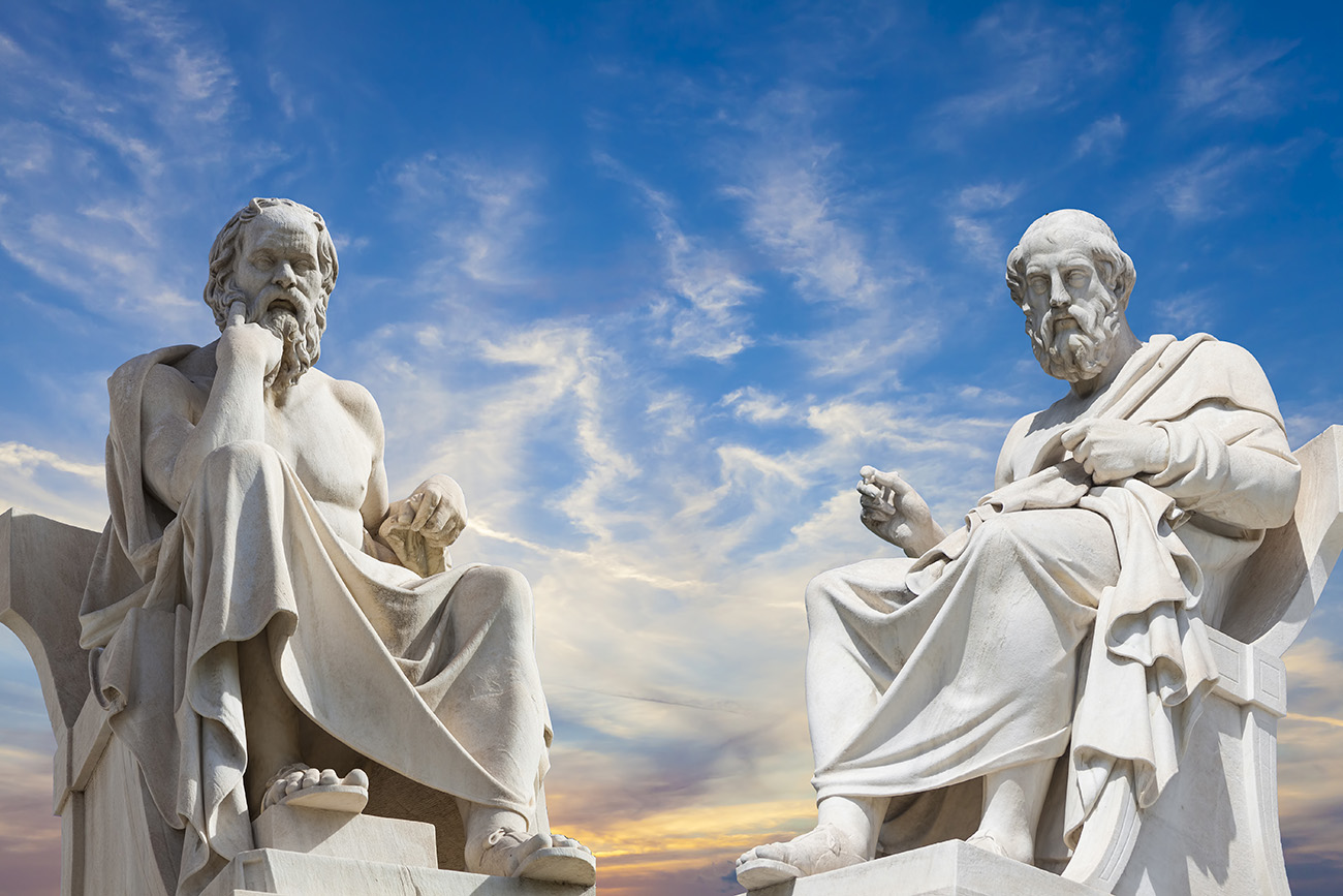 Statues of ancient philosophers against a deep blue sky.