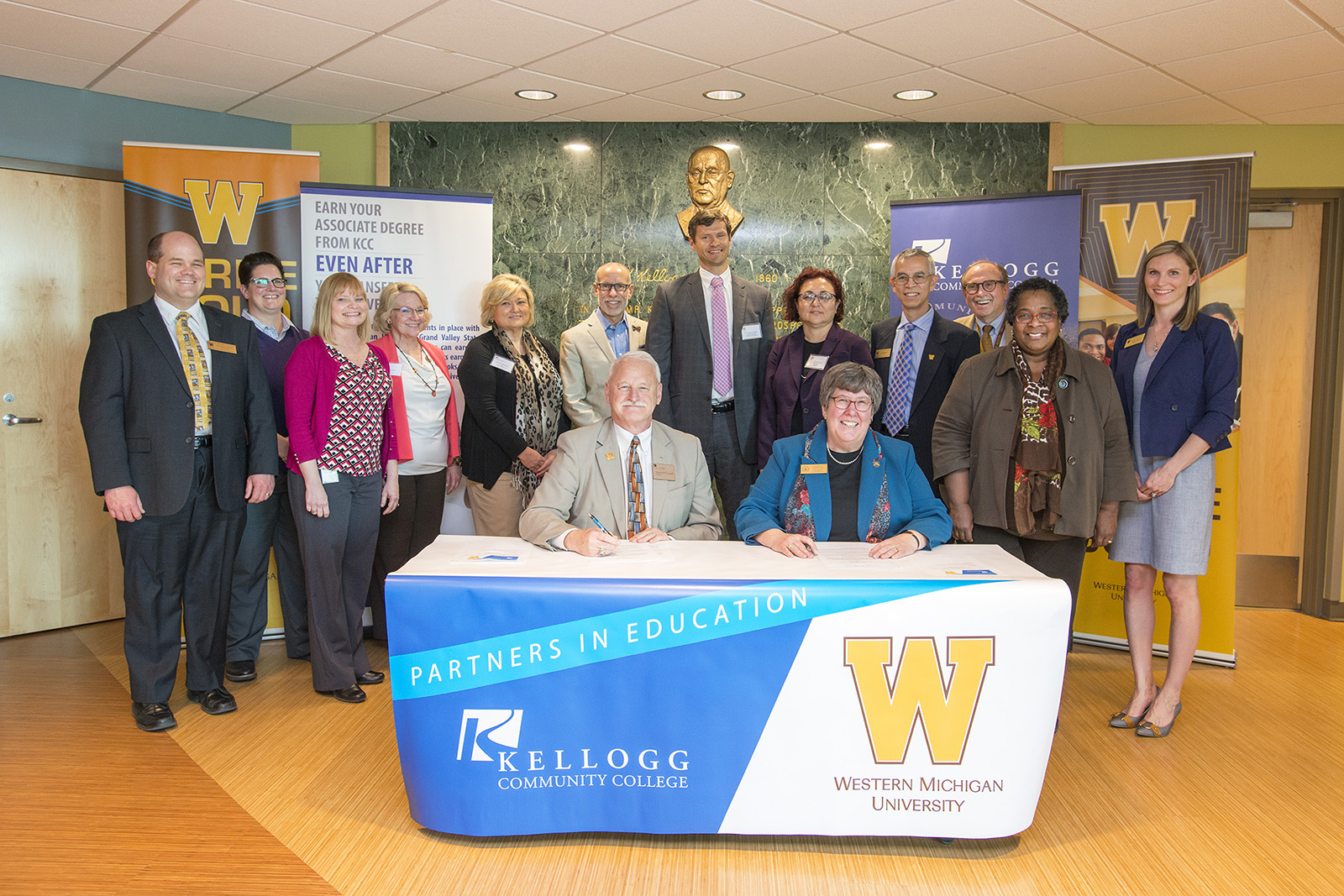 KCC President Mark O'Connell and Dr. Susan Stapleton, interim provost and vice president for academic affairs at Western Michigan University, sign a formal articulation agreement with other KCC and WMU officials in the Kellogg Room of KCC's North Avenue campus in Battle Creek on May 1, 2018.