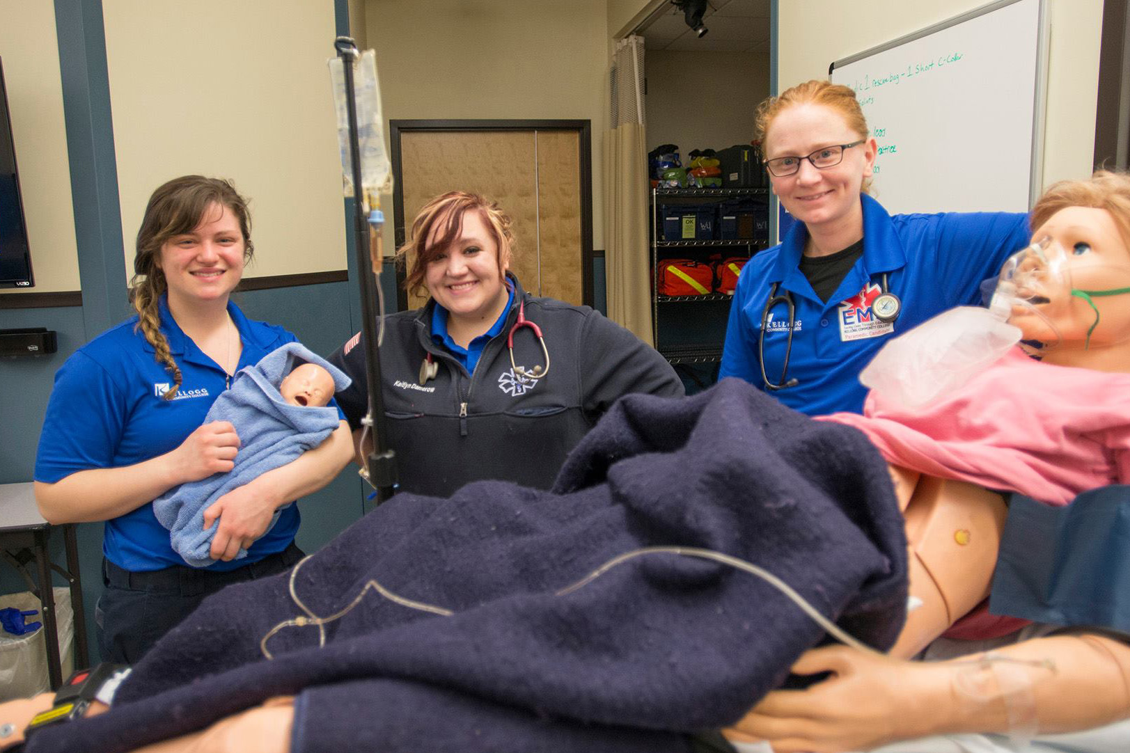 Paramedic students pose for a photo following a birthing simulation on campus.