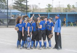 The KCC softball team meets on the field during a home game.