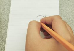 A closeup of a hand drawing with a pencil on a notepad.