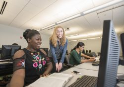 English professor Elyse Jozlin works with a student in a computer lab at KCC.
