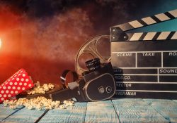 A stock photo showing retro film production accessories placed on wooden planks to communicate the concept of filmmaking.