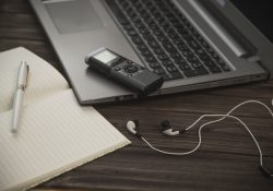 A notebook, pen, laptop, voice recorder and headphones arranged in a stock photo demonstrating the tools of a journalist.