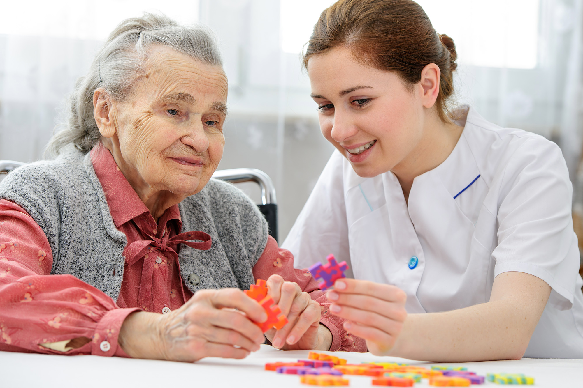 Stock photo of an elder care nurse playing a jigsaw puzzle with a senior woman in a nursing home.