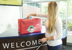 A student puts a donation into an Operation Christmas Child donation box on campus in Battle Creek.
