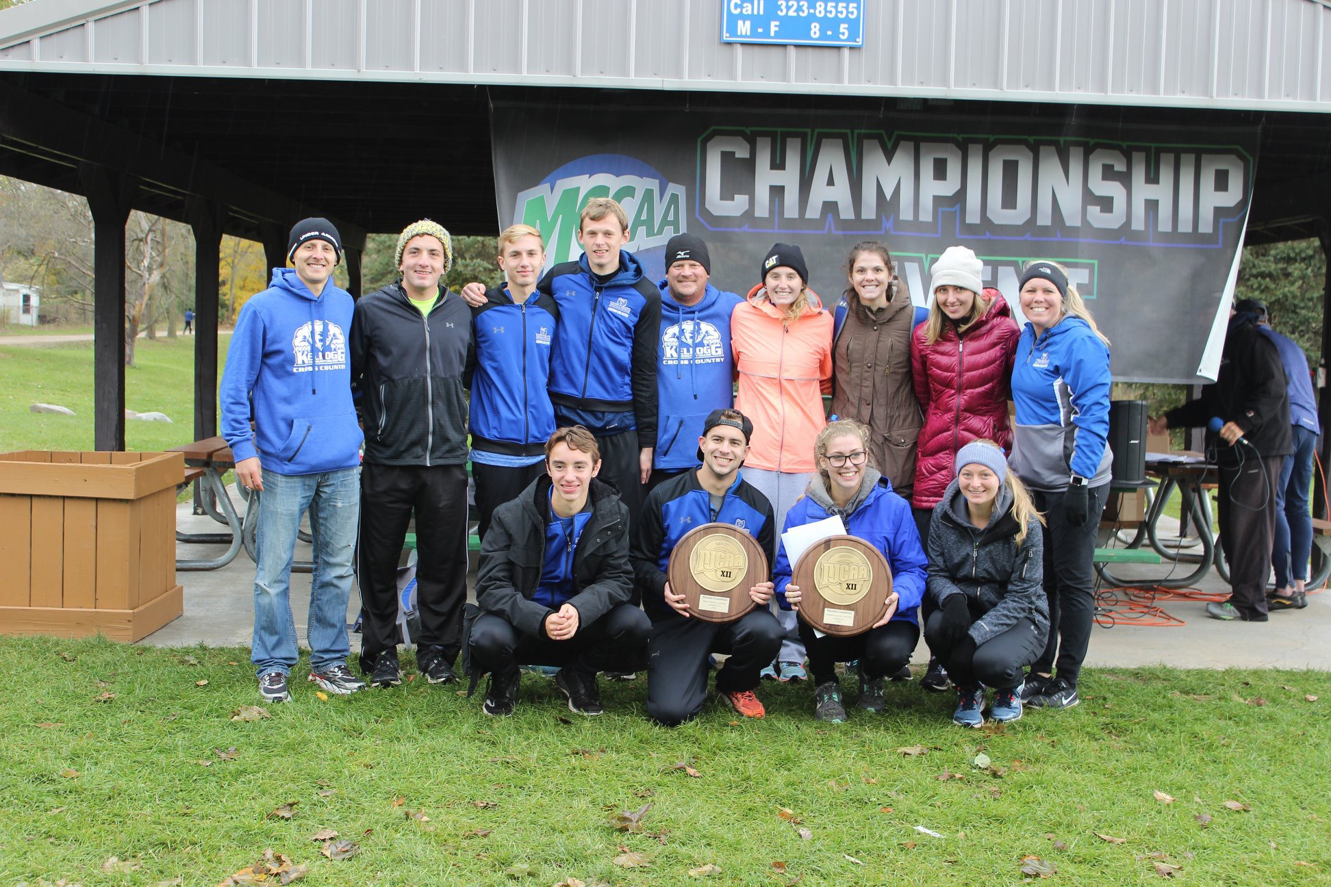 KCC's men's and women's cross-country teams pose with trophies won for winning their respective regional championships.