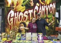 KCC alum and comic creators Angie and Aaron Warner stand at a comic book display featuring their newest title, Ghost Canyon.