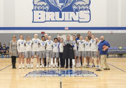 Former Battle Creek mayor Al Bobrofsky, who officiated the College's first basketball game in 1966, poses with wife Ann, the KCC women's basketball team and college officials before the start of the women's basketball game on Dec. 5, 2018.