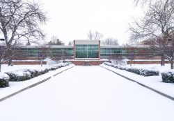 An exterior view of the main entrance to KCC's North Avenue campus in Battle Creek, covered in snow.