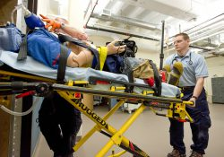 EMS students push a simulated patient on a gurney in the College's EMS sim lab.