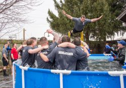 A KCC Police Academy cadet jumps into a pool during a polar plunge event in 2017.